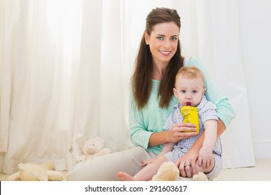 Mother giving baby a drink at home