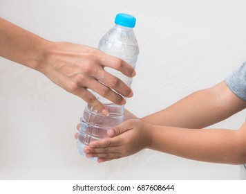 Mother giving a bottle of crystal clear drinking water to her child. Love and care concept.