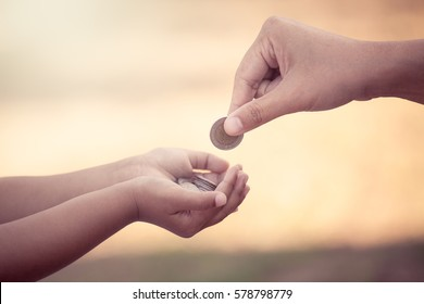 Mother giving coin to child as saving money concept in vintage color tone