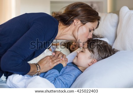 Mother giving good night kiss to sleeping son. Lovely mother putting son to  bed. 7531a30f2
