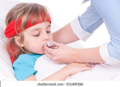 Mother giving her daughter cough syrup at home. Sick little girl in bed taking medicine with plastic cup.