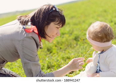 mother giving her daughter flower to smell