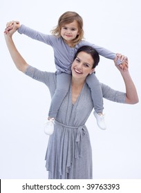Mother giving her daughter piggyback ride at home against white background