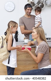 Mother giving her daughter the school lunch in the kitchen