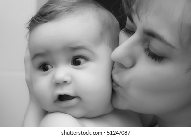 Mother giving a kiss to her little happy baby baby boy; black and white