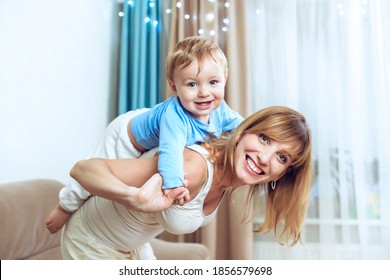 Mother giving piggyback ride to happy cute small son, enjoying active leisure time. Laughing woman carrying on back little baby boy playing, having fun together.