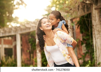 Mother giving piggyback ride to her loving daughter