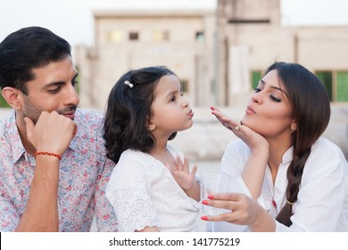 mother giving water to her daughter while father looking at them, portrait of indian family