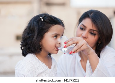 mother giving water to little daughter, indian mother and daughter
