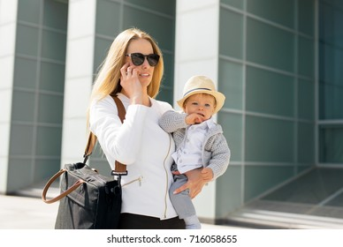 Mother going to work and talking on the phone with baby in her hands