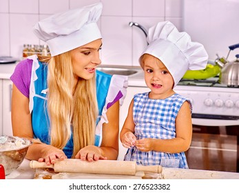 Mother and granddaughter in hat baking cookies.