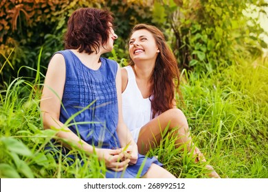 mother with grown up daughter sitting on a grass and affectionately talking