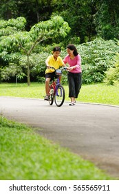 Mother guiding son on bicycle