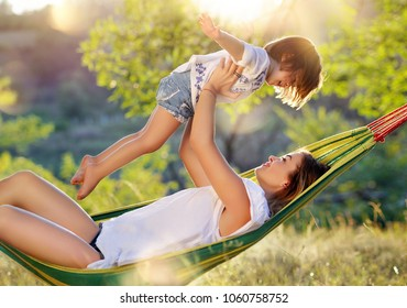 Mother in hammock playing with daughter in aiplane game holding her in the air