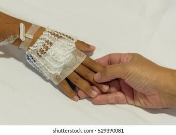 Mother hand holding children hand on IV set.Medical care concept.