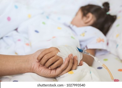 Mother hand holding sick daughter hand who have IV solution bandaged with love and care while she is sleeping on bed in the hospital