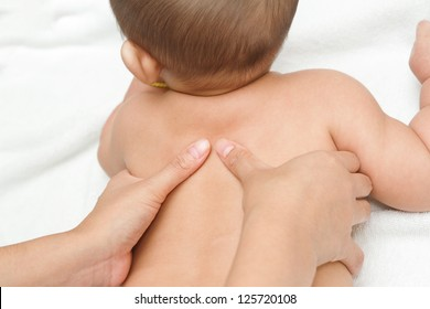 Mother hand massaging back muscle  of her baby,touch of Happiness