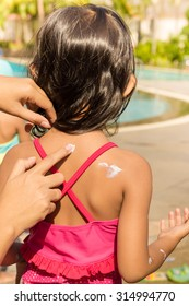 Mother Hand Putting Sunblock Lotion on Little Girl Back Skin Before Swimming