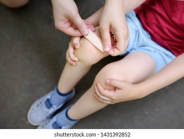 Mother hands applying antibacterial medical adhesive plaster on child's knee after falling down. First aid for kids after injury/trauma