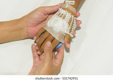 Mother hands holding children hand on IV set.Medical care concept.