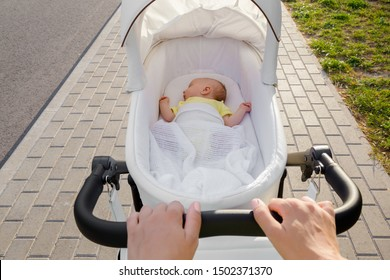 Mother hands pushing white baby stroller. Daily outside walking. Infant sleeping and breathing fresh air in summer. Point of view shot.