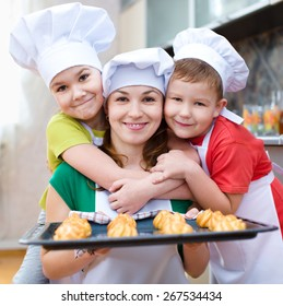 Mother with happy children making bread in the kitchen