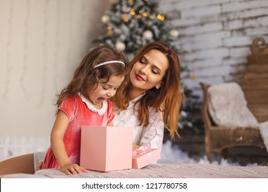 Mother with happy daughter looking inside of Christmas gift box. Happy Toddler girl looking at Christmas present box. Little girl open pink gift box