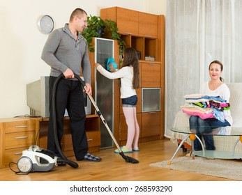 Mother, happy father and little girl doing general cleaning indoors
