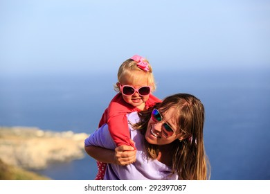 mother and happy little daughter play on summer sky