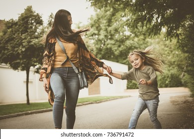 Mother have fun with daughter at street.