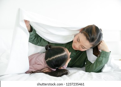 Mother having fun with their little daughter on bed . Family spending time at the holiday , happy family concept.