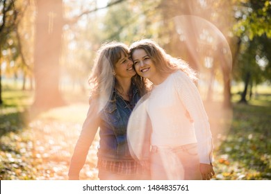 Mother having great time with her adult daughter outdoor in park - flare visible