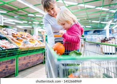 Mother having her toddler girl riding in shopping cart of supermarket