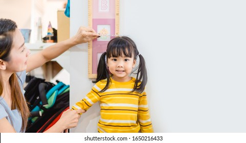 Mother Height measure her daughter near white wall at home.2.6 years old girl kid standing and looking at above using hand measuring her height.Growth hormones, child development, Calcium concept.