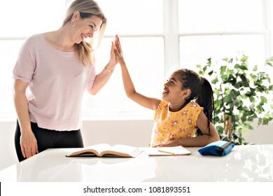mother help Black girl doing homework at home