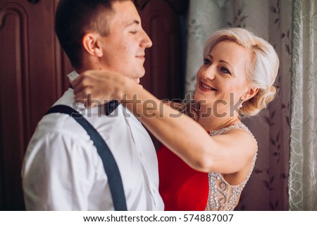 Mother is helping with a bow-tie to her son before wedding ceremony.