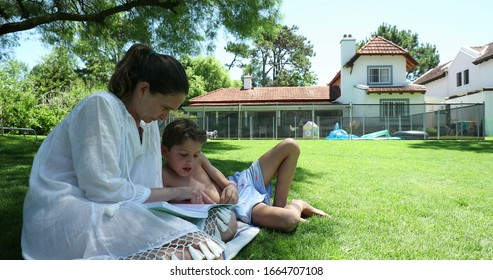 Mother helping child to study, teaching to read, outside in home backyard lawn