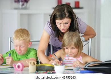 Mother helping children to do homework