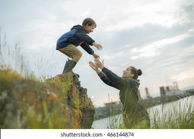mother Helping Children To Jump Off Rocks