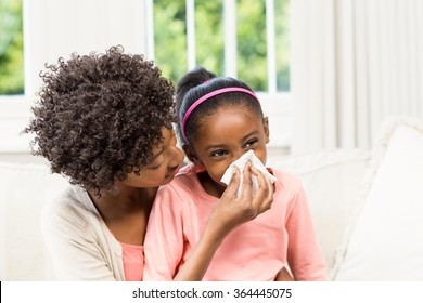 Mother helping daughter blowing her nose on sofa