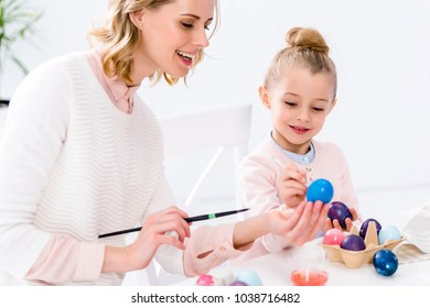 Mother helping daughter to color Easter eggs
