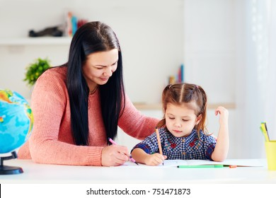 mother helping daughter to develop writing skills at home
