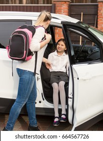 Mother helping daughter to get inside the car after school lessons
