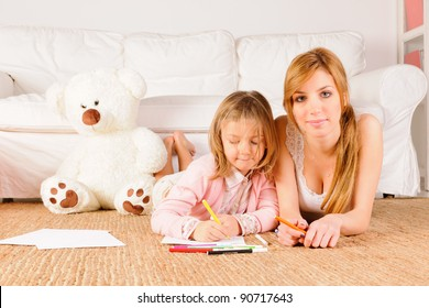 Mother helping daughter with homeworks. Painting and drawing