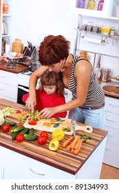 Mother helping daughter making salad