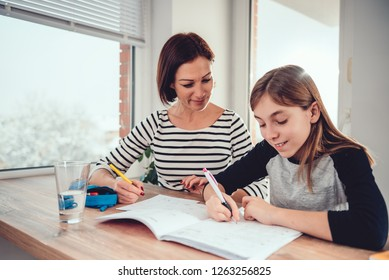 Mother helping daughter with math homework by the window at dining table