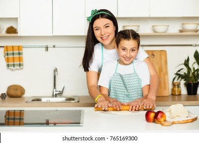Mother helping daughter preparing food, rolling a dough. Staying at home at white kitchen, laughing and looking at camera. Family leisure at home