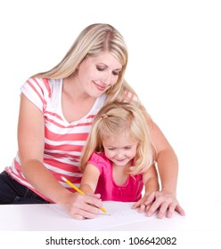 Mother helping daughter write alphabet, sitting at a desk