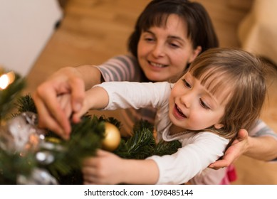 Mother helping her adorable daughter in decorating christmas tree