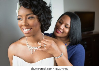 Mother helping her daughter get dressed for her wedding.